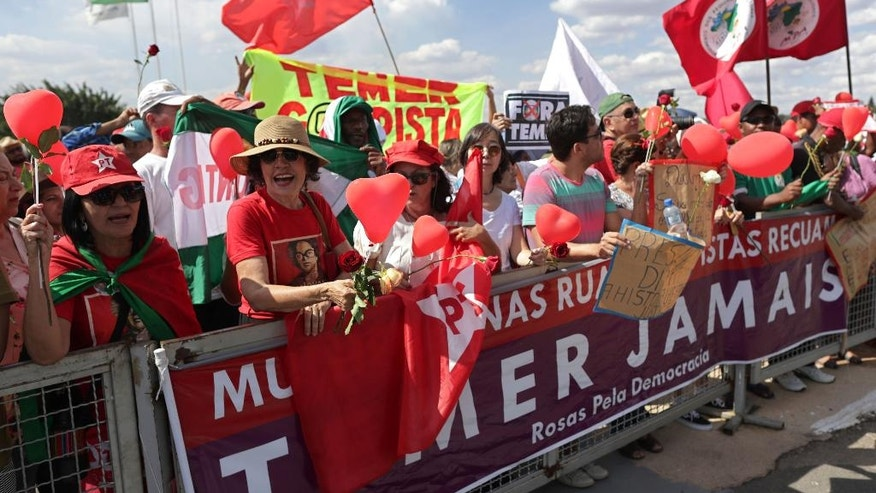 In this Sept. 6, 2016 photo, members of the Worker's Party and Landless Worker's Movement rally in support of Brazil's impeached President Dilma Rousseff on the day she permanently leaves the presidential residence, outside Alvorada Palace in Brasilia, Brazil. Over more than a decade, the Workers' Party was credited with pulling millions of people out of poverty via social works programs, progressive laws like raising the minimum wage and a political discourse focused more on the have-nots than the wealthy. (AP Photo/Eraldo Peres)