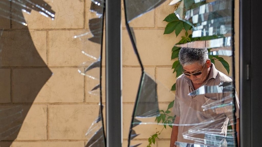 FILE - In this Aug. 30, 2016, file photo, a Chinese Embassy employee examines broken windows at the Chinese Embassy after a suicide bombing in Bishkek, Kyrgyzstan. The suicide bombing of the embassy highlighted the expanding threat of an ethnic Uighur militant group called the East Turkestan Islamic Movement - and the growing Chinese involvement in Syria and Afghanistan to combat it. The ETIM, also known as the Turkistan Islamic Party, has sought for decades to establish an independent state in China's far west for the repressed Muslim Uighur minority. (AP Photo/File)