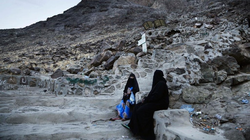 Women sit on steps of Noor Mountain, where Prophet Muhammad received his first revelation from God to preach Islam, on the outskirts of Mecca, Saudi Arabia, Friday, Sept. 9, 2016. Muslim pilgrims have begun arriving at the holiest sites in Islam ahead of the annual hajj pilgrimage in Saudi Arabia. (AP Photo/Nariman El-Mofty)