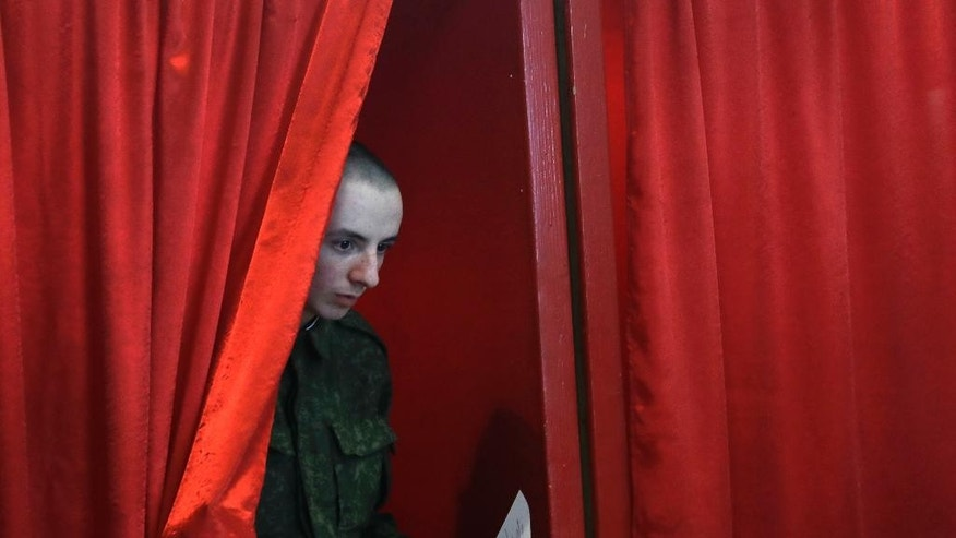 A Belarusian soldier leaves a voting booth at a polling station during early voting in Minsk, Belarus, Tuesday, Sept. 6, 2016. The early voting is conducted five days before parliamentary elections on Sunday, Sept. 11. (AP Photo/Sergei Grits)