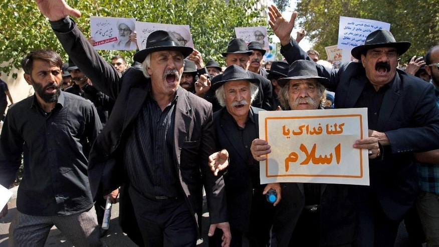 "Iranian protesters chant slogans as one of them holds a placard reading ""oh Islam! we will sacrifice our lives for you"", after weekly Friday prayer in Tehran, Iran, Sept. 9, 2016. Thousands of Iranians marched through the streets Friday to protest Saudi Arabia ahead of the hajj, a sign of soured relations between the two countries following last year's crush and stampede during the annual pilgrimage. (AP Photo/Ebrahim Noroozi)"