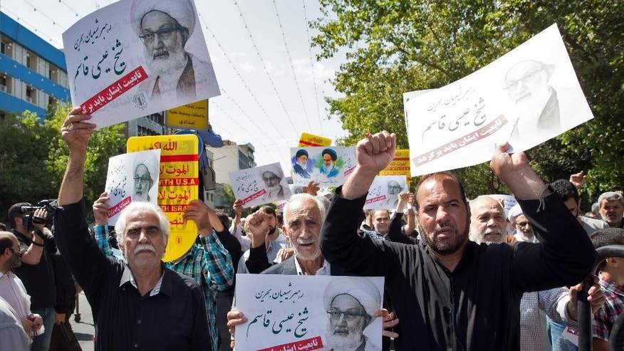 Iranian protesters hold placards with pictures of Ayatollah Sheik Isa Qassim, Bahrain's top Shiite Muslim cleric during an anti-Saudi rally after weekly Friday prayer in Tehran, Iran, Friday, Sept. 9, 2016. Thousands of Iranians marched through the streets Friday to protest Saudi Arabia ahead of the hajj, a sign of soured relations between the two countries following last year's crush and stampede during the annual pilgrimage. (AP Photo/Ebrahim Noroozi)