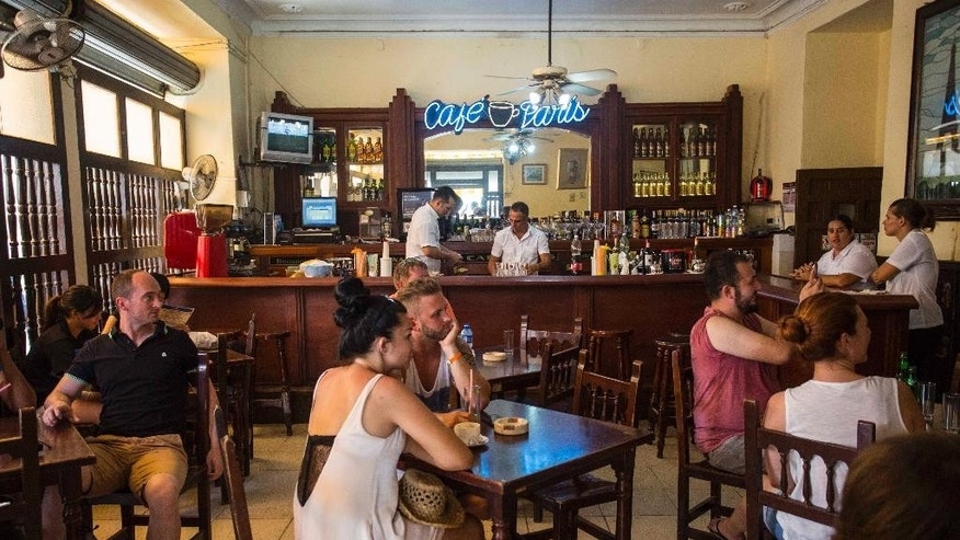 Tourists sit in the Cafe Paris, in Old Havana, Cuba, Thursday, Sept. 8, 2016. Over a quarter century, the City's Historian office turned Old Havana into a painstakingly restored colonial jewel, a tourist draw that brings in more than $170 million a year, according to the most recent available figures. The office became a center of power with unprecedented budgetary freedom from the island's communist central government. Last month, the Cuban military took over the business operations of the City Historian's Office, taking away its independence. (AP Photo/Desmond Boylan)