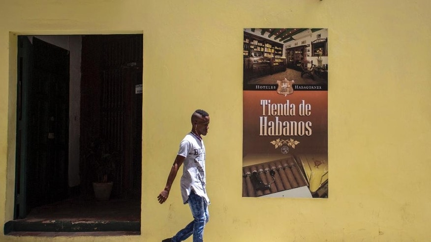 A youth walks beside a cigar store of the Habaguanex company in Old Havana, Cuba, Thursday, Sept. 8, 2016. The largest business arm of the City Historian's Office, Habaguanex, named for a pre-Columbian indigenous chief, directly runs some 20 hotels and 30 stores and more than 25 restaurants in Old Havana. Last month, the Cuban military took over the business operations of the City Historian's Office, including Habaguanex. (AP Photo/Desmond Boylan)
