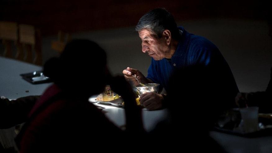 In this Wednesday, Sept. 7, 2016 photo, Odilon Velarde, 61, has lunch in a soup kitchen organized by the Catholic Church in Lima, Peru. While Velarde spent less than 50 cents a day for his meal, across town high-priced dishes reflecting the country's African, Asian, European and indigenous roots are being featured at some 200 pop-up restaurants during Latin America's largest culinary festival. (AP Photo/Rodrigo Abd)