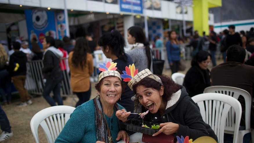 In this Tuesday, Sept. 6, 2016 photo, women pose for a photo at the gastronomic fair Mistura, in Lima, Peru. President Pedro Pablo Kuczynski kicked off this year's edition on a solemn note reminding his compatriots that not everyone can savor Peru's culinary richness. (AP Photo/Rodrigo Abd)