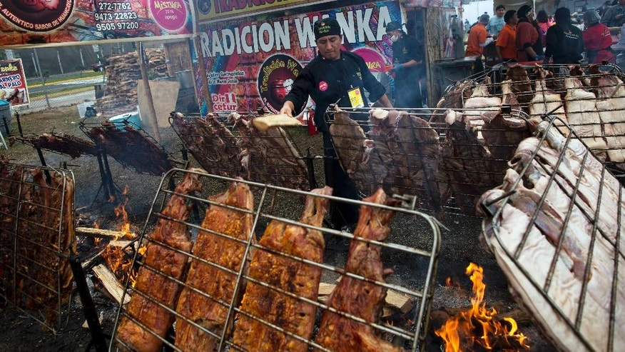 In this Tuesday, Sept. 6, 2016 photo, a chef tends the fires at the gastronomic fair Mistura, in Lima, Peru. The foodie fair annually attracts about half a million people over nine days, including 35,000 foreigners. For the most part, poor Peruvians are unseen at Mistura except working in the kitchen and cleaning the dishes left by better-off patrons. (AP Photo/Rodrigo Abd)