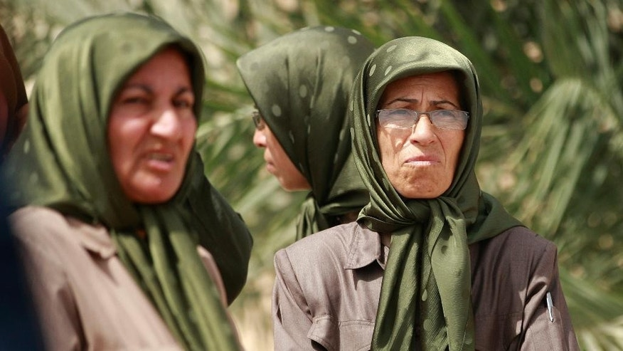 FILE - In this Tuesday, Sept. 11, 2012 file photo, members of the Mujahedeen-e-Khalq organization seen inside the Liberty refugee camp in Baghdad, Iraq. The Iranian opposition group said Friday, Sept. 9, 2016 that a camp housing its members in Iraq has been officially closed after the last 280 residents were flown to Albania. The Mujahedeen-e-Khalq has been based in Iraq since the 1980s, when they received arms and support from Saddam Hussein during the Iran-Iraq war.(AP Photo/Hadi Mizban, File)
