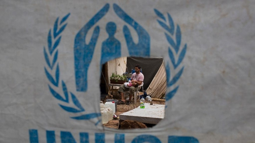 A Syrian man feeds his child behind a UNHCR plastic sheet at Ritsona refugee camp, north of Athens, which hosts about 600 refugees and migrants on Thursday, Sept. 8, 2016. The refugee crisis is expected to be a central issue in discussions Friday at a meeting in Athens of leaders from Mediterranean countries in the European Union. (AP Photo/Petros Giannakouris)