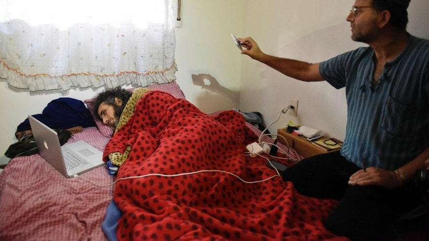 Syrian native Abu Wa'el Dhiab, a former Guantanamo detainee, lies in bed as he speaks to his family via a laptop, in his apartment in Montevideo, Uruguay,Friday, Sept. 9, 2016. Activists and Uruguayan officials say the health of the former Guantanamo detainee resettled in the South American country is deteriorating as he continues a hunger strike at his home. Dhiab is demanding to leave Uruguay, which took him in with five other former Guantanamo prisoners in 2014. (AP Photo/Matilde Campodonico)