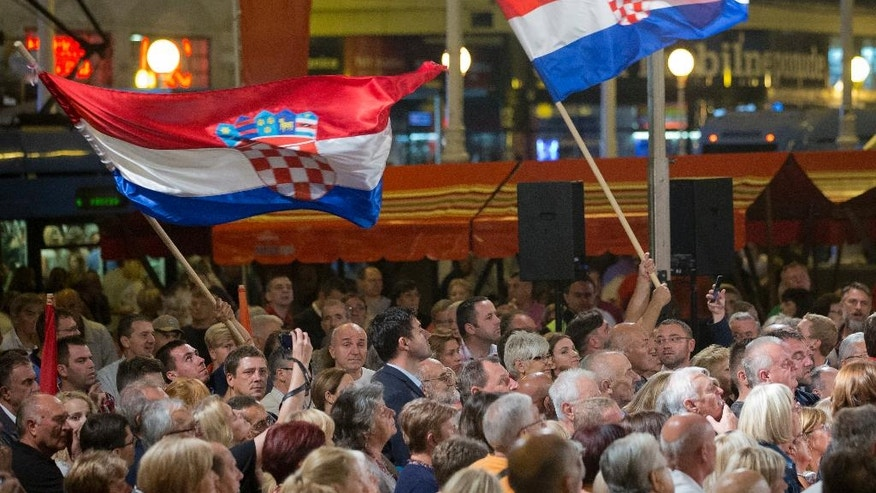 In this photo taken late Wednesday, Sept. 7, 2016, supporters of center-left coalition wave flags at a rally in Zagreb, Croatia. Croats go to the polls this weekend in a snap election that, despite the country's many problems, has been more about past divisions than future challenges facing the European Union's newest member state. (AP Photo/Darko Bandic)