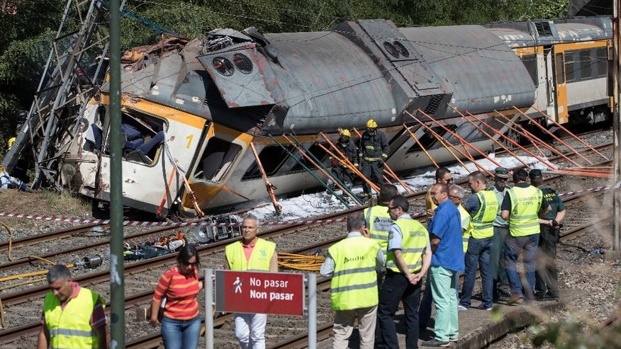 CORRECTS DATE  - Emergency personnel attend the scene after a passenger train traveling from Vigo to Porto, in neighboring Portugal, derailed in O Porrino,  in Spain's northwestern Galicia region, killing  and injuring people, authorities said Friday Sept. 9, 2016. The train had three cars. The front one came completely off the track and hit a post next to the line, leaving it leaning to one side. The back two cars were partly off the tracks. Spanish media said the train was carrying around 60 passengers.(AP Photo/Lalo R. Villar)