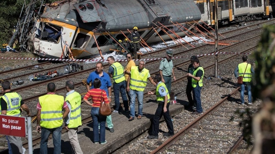 CORRECTS DATE  Emergency personnel attend the scene of a passenger train traveling from Vigo to Porto, in neighboring Portugal, that derailed in O Porrino, in  Spain's northwestern Galicia region, killing  and injuring people, authorities said  Friday, Sept. 9, 2016  . The train had three cars. The front one came completely off the track and hit a post next to the line, leaving it leaning to one side. The back two cars were partly off the tracks. Spanish media said the train was carrying around 60 passengers.(AP Photo/Lalo R. Villar)