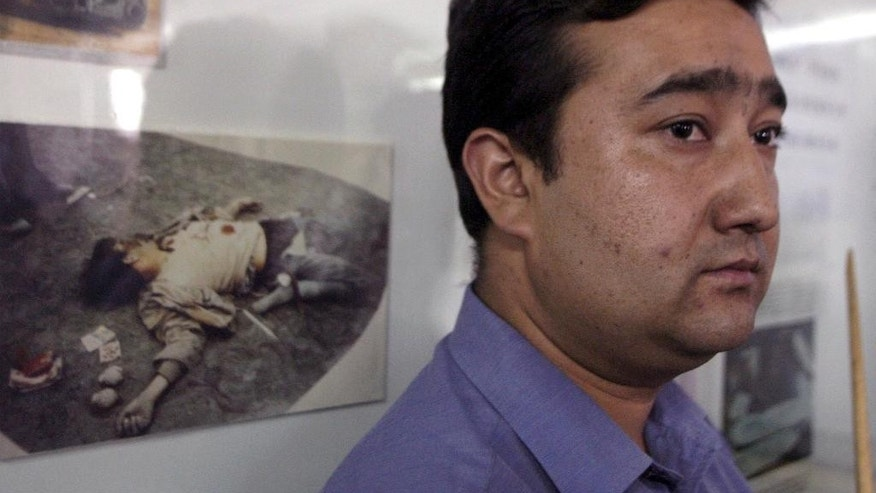 FILE - In this Sept. 15, 2003, file photo, a Uighur official stands near a picture of a dead separatist militant at an exhibition in Hotan in China's western Xinjiang province. Since 2015 militants belonging to the Uighur ethnic group native to the vast Xinjiang region in western China have shown signs of becoming a force in Islamic extremism globally, a development that is reshaping both the ground war in Syria and Chinese foreign policy. (AP Photo/Ng Han Guan, File)