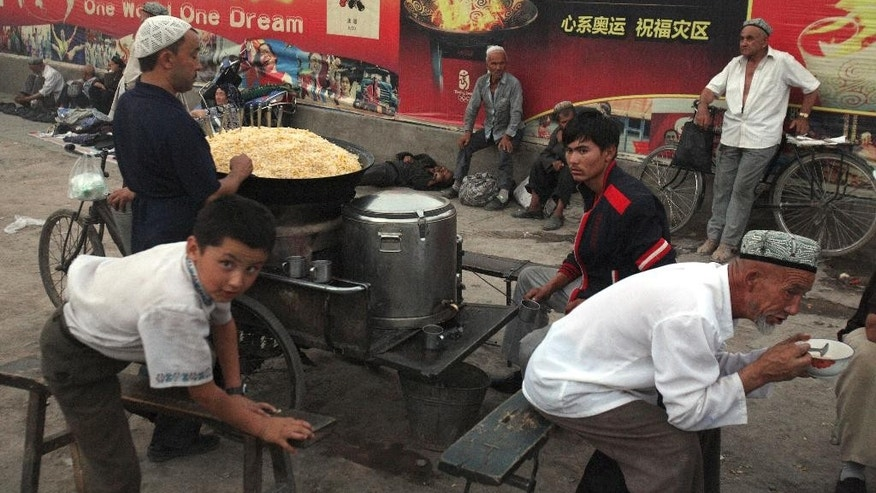 FILE - In this Aug. 6, 2008, file photo, Uighurs rest near a food stall and Beijing Olympic Games billboards in Kashgar in China's western Xinjiang province. Since 2015 militants belonging to the Uighur ethnic group native to the vast Xinjiang region in western China have shown signs of becoming a force in Islamic extremism globally, a development that is reshaping both the ground war in Syria and Chinese foreign policy. (AP Photo/Ng Han Guan, File)