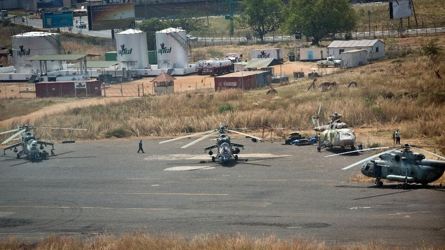 FILE - In this Monday, Dec. 30, 2013 file photo, military helicopter gunships sit parked at the airport in Juba, South Sudan. A confidential U.N. report obtained by The Associated Press on Friday, Sept. 9, 2016 says South Sudan's deadly fighting in July was directed by the highest levels of government, and that leaders are intent on a military solution that worsens ethnic tensions. (AP Photo/Ben Curtis, File)