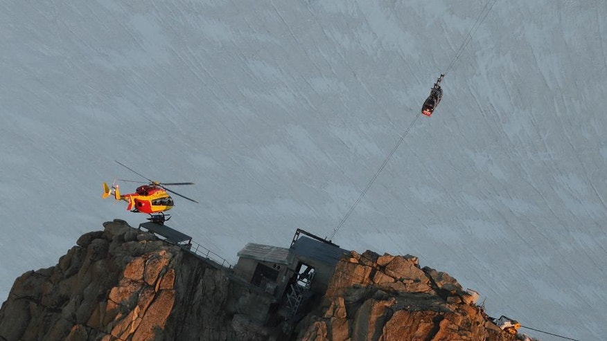 An EC-135 helicopter operated by the French Societe' Civile hovers, Friday, Sept. 9, 2016, near three cars of the Panoramic Mont Blanc cable car that stalled around 4 p.m. (1400 GMT) on Thursday, after its cables reportedly tangled. The cable car carrying 110 tourists stopped working at high altitude over the Mont Blanc massif in the Alps on Thursday, prompting a major rescue operation and leaving 45 people trapped in midair overnight, France's interior minister said. (AP Photo/Luca Bruno)