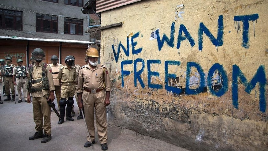 FILE - In this Aug. 12, 2016, file photo, Indian policemen stand guard during a curfew in Srinagar, Indian-controlled Kashmir. As Kashmir enters a third month of tense conflict marked by violent street clashes and almost daily protests following the July 8, 2016 killing of charismatic rebel leader Burhan Wani, Indian government troops backed by local police are maintaining a tight security lockdown throughout the region. That's left the local Kashmiri police, tasked with patrolling the streets, gathering intelligence and profiling anti-India activists, feeling demoralized, afraid and caught in the middle between the Indian authorities who employ them and the friends and neighbors who question their loyalties. (AP Photo/Dar Yasin, File)
