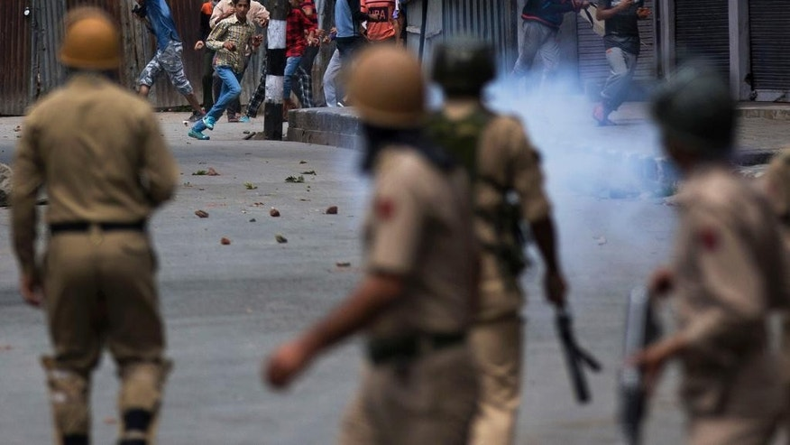 FILE - In this Aug. 31, 2016, file photo, Kashmiri protesters face Indian policemen in Srinagar, Indian controlled Kashmir. As Kashmir enters a third month of tense conflict marked by violent street clashes and almost daily protests following the July 8, 2016 killing of charismatic rebel leader Burhan Wani, Indian government troops backed by local police are maintaining a tight security lockdown throughout the region. That's left the local Kashmiri police, tasked with patrolling the streets, gathering intelligence and profiling anti-India activists, feeling demoralized, afraid and caught in the middle between the Indian authorities who employ them and the friends and neighbors who question their loyalties. (AP Photo/Dar Yasin, File)