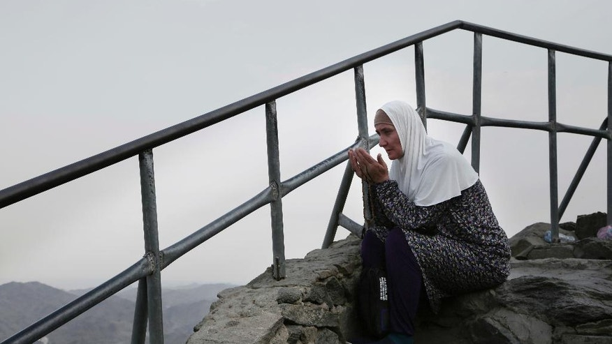 Turkish woman prays on top of Noor Mountain, where Prophet Muhammad received his first revelation from God to preach Islam, on the outskirts of Mecca, Saudi Arabia, Friday, Sept. 9, 2016. Muslim pilgrims have begun arriving at the holiest sites in Islam ahead of the annual hajj pilgrimage in Saudi Arabia. (AP Photo/Nariman El-Mofty)