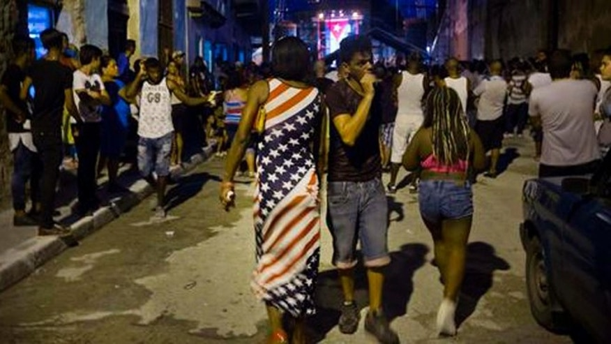 A woman wearing a dress with a U.S. flag motif walks to a concert by Silvio Rodriguez in Guanabacoa on the outskirts of Havana, Cuba, Friday, Sept. 9, 2016. President Barack Obama's easing of the U.S. trade embargo on Cuba has had virtually no positive effect on the island's economy, Cuba's top diplomat asserted Friday. (AP Photo/Ramon Espinosa)