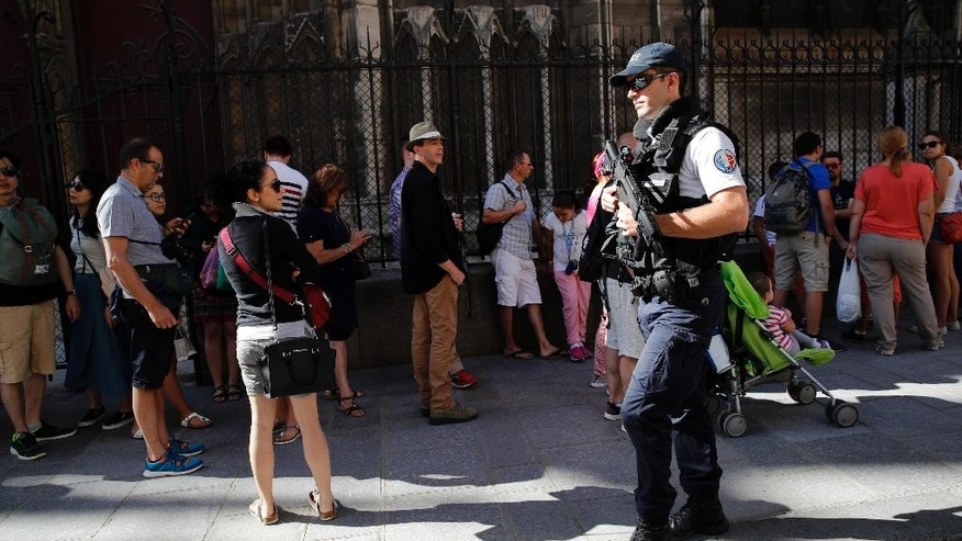 A French police officer patrols in front of Notre Dame cathedral, in Paris, Friday Sept. 9, 2016. A failed attack involving a car loaded with gas canisters near Notre Dame Cathedral was spearheaded a group of women that included a 19-year-old whose written pledge of allegiance to the Islamic State group was found by police, a security official said Friday. (AP Photo/Christophe Ena)