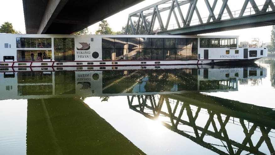 A river cruise ship sticks underneath a railway bridge on the Main-Danube Canal near Erlangen, Germany, Sunday Sept. 11, 2016. Authorities say the  river cruise ship hit a rail bridge in southern Germany, crushing the wheelhouse and leaving two crew members dead. The ship had just cast off early Sunday from the town of Erlangen on its way to the Hungarian capital, Budapest, along the Main-Danube Canal when the accident occurred, the news agency dpa reported. The dead were a 49-year-old who was at the wheel of the vessel and a 33-year-old sailor. ( Nicolas Armer/dpa via AP)