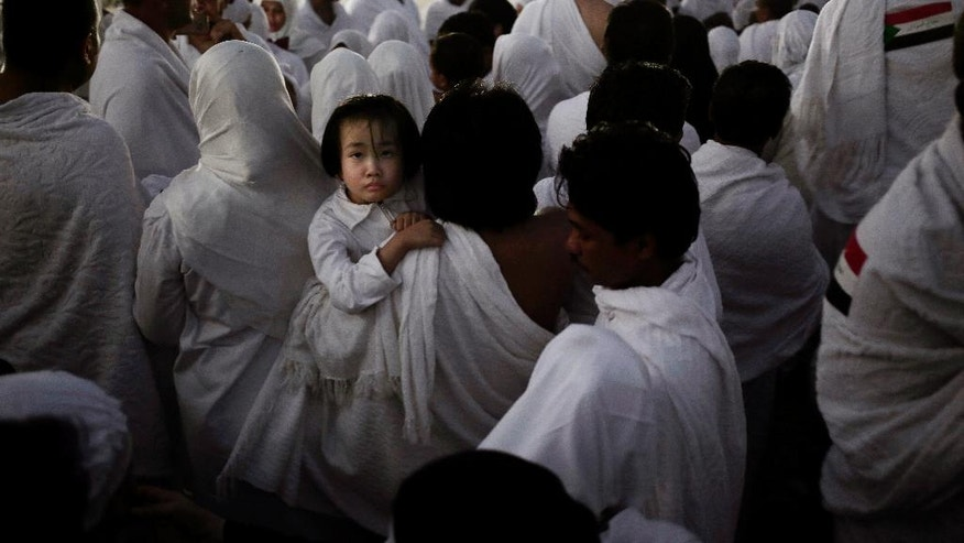 An Indonesian father carries his daughter through the crowd after reaching the top of a rocky hill known as Mountain of Mercy, on the Plain of Arafat, during the annual hajj pilgrimage, ahead of sunrise near the holy city of Mecca, Saudi Arabia, Sunday, Sept. 11, 2016. Mount Arafat, marked by a white pillar, is where Islam's Prophet Muhammad is believed to have delivered his last sermon to tens of thousands of followers some 1,400 years ago, calling on Muslims to unite. (AP Photo/Nariman El-Mofty)