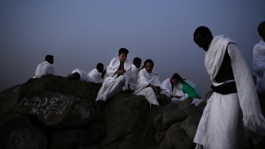 Muslim pilgrims pray on a rocky hill known as Mountain of Mercy, on the Plain of Arafat, during the annual hajj pilgrimage, ahead of sunrise near the holy city of Mecca, Saudi Arabia, Sunday, Sept. 11, 2016. Mount Arafat, marked by a white pillar, is where Islam's Prophet Muhammad is believed to have delivered his last sermon to tens of thousands of followers some 1,400 years ago, calling on Muslims to unite. (AP Photo/Nariman El-Mofty)
