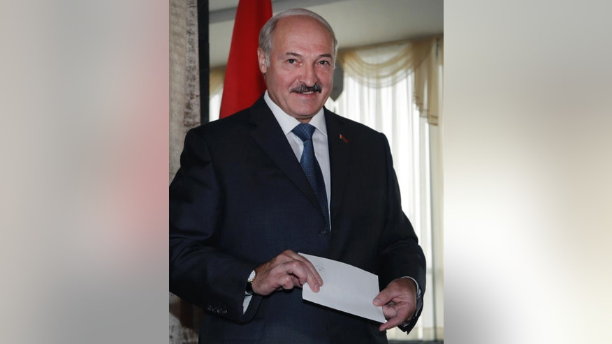 Belarusian President Alexander Lukashenko smiles at photographers as he prepares to cast his ballot during parliamentary elections in Minsk, Belarus, Sunday, Sept. 11, 2016. Belarusians are casting ballots for a new parliament in the authoritarian former Soviet republic that has been making steps toward rapprochement with the West. (AP Photo/Sergei Grits)