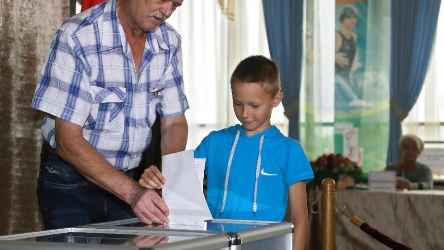 A Belarusian man casts his ballot with a boy at a polling station during parliamentary elections in Minsk, Belarus, Sunday, Sept. 11, 2016. Belarusians are casting ballots for a new parliament in the authoritarian former Soviet republic that has been making steps toward rapprochement with the West. (AP Photo/Sergei Grits)