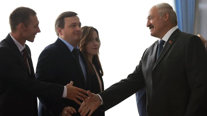 Belarusian President Alexander Lukashenko, right, shakes hands with an observer as he arrives at a polling station during parliamentary elections in Minsk, Belarus, Sunday, Sept. 11, 2016. Belarusians are casting ballots for a new parliament in the authoritarian former Soviet republic that has been making steps toward rapprochement with the West. (AP Photo/Sergei Grits)