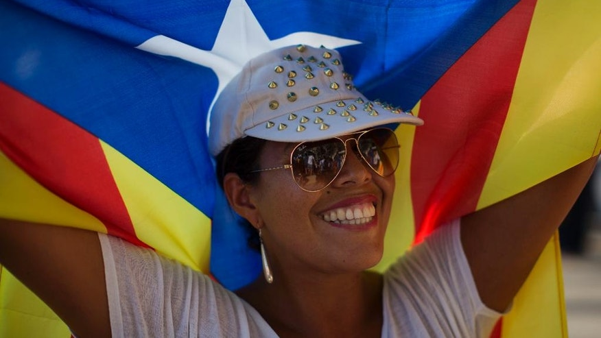 """A woman holds an """"estelada"""" flag, that symbolize Catalonia's independence, during a demonstration calling for the independence of Catalonia, in Barcelona, Spain, Sunday, Sept. 11, 2016. The leader of Spain's powerful northeastern region of Catalonia has said he plans to propose a government-approved binding independence referendum to secede from Spain by next year. Catalonia's separatist leader, Carles Puigdemont, spoke Saturday at a news conference before celebrations of the Catalan National Day holiday, which separatists have used for years to rally hundreds of thousands in support of a new European nation. (AP Photo/Emilio Morenatti)"""