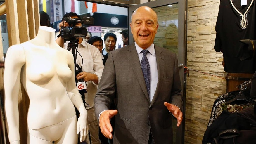 FILE - In this Sept. 8, 2016 file photo, Alain Juppe, former French Prime Minister and mayor of Bordeaux, walks in a fashion shop as he visits the Chinese Fashion Center at Aubervilliers, in the outskirts of Paris. Nine contenders formally declared their candidatures for France's conservative presidential primary Friday, Sept. 9 2016, but the race is expected to come down to a tight battle between former president Nicolas Sarkozy and former prime minister Alain Juppe. (AP Photo/Francois Mori, File)