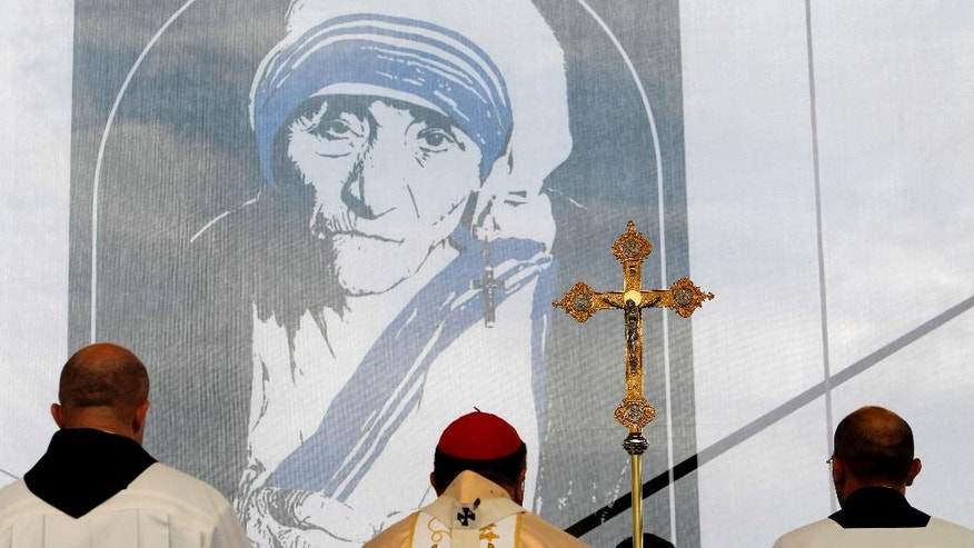 A portrait of Mother Teresa is pictured behind a crucifix, during a holy Mass dedicated to her on the main square in Skopje, Macedonia, Sunday, Sept 11, 2016. Hundreds of people gathered Sunday at the main square in Macedonian capital Skopje for a ceremony of gratitude dedicated to Mother Teresa who Pope Francis has declared a saint last week in Vatican. (AP Photo/Boris Grdanoski)