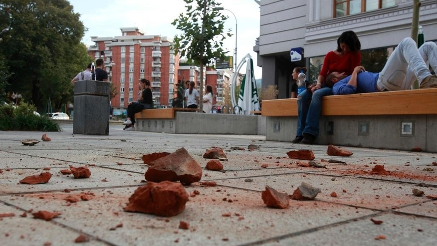 People sit outside buildings near fallen bricks, after an earthquake in Skopje, Macedonia, Sunday, Sept. 11, 2016. Macedonian authorities say an earthquake with a preliminary magnitude of 5.3 struck on the outskirts of the capital, Skopje, Sunday causing minor damage to buildings but no injury. (AP Photo/Boris Grdanoski)