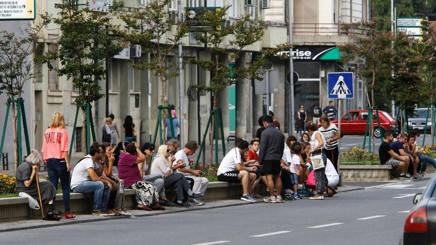 People sit in a street outside their homes, after an earthquake in Skopje, Macedonia, Sunday, Sept. 11, 2016. Macedonian authorities say an earthquake with a preliminary magnitude of 5.3 struck on the outskirts of the capital, Skopje, Sunday causing minor damage to buildings but no injury. (AP Photo/Boris Grdanoski)