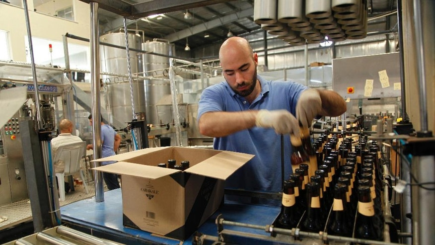 In this Tuesday, Sept. 6, 2016 photo, Carakale Brewery staffer Ramzi Kharoufeh fills a box with beer bottled, pasteurized and labeled that day in Fuheis, Jordan. The maker of Jordan's first craft beer, Carakale, is part of a small but growing group of Arab brewers in the Levant who want to nurture local beer-drinking cultures and compete against large companies that dominate the region's growing beer market. (Sam McNeil/AP Photo)