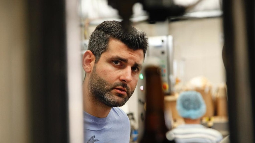 In this Tuesday, Sept. 6, 2016 photo, Yazan Karadsheh, founder of the Carakale Brewery in Fuheis, Jordan, watches a machine fill beer bottles and cap them on an assembly line. The Jordanian microbrew is starting to export to the United States its signature blonde, Indian pale ale, and a coffee porter dosed with roasted cardamom. (AP Photo/Sam McNeil)