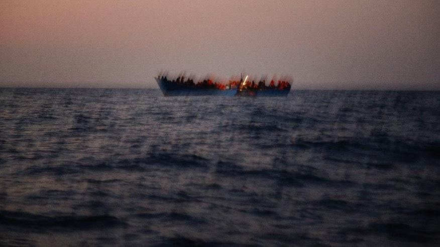 "FILE - In this Monday, Aug. 29, 2016 file photo, migrants crowd onto a wooden boat as they wait to be rescued, on the Mediterranean sea, about 13 miles north of Sabratha, Libya. When the camera's viewfinder is in ""night vision"" mode, a hidden world appears that is invisible to the naked eye in the darkness of night. Bathed in green, the view is even more dreamlike _ or nightmarish. (AP Photo/Emilio Morenatti, File)"