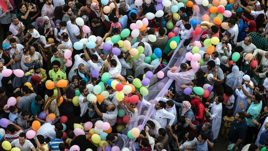 Egyptians try to catch balloons distributed for free after Eid Al-Adha prayers outside al-Seddik mosque in Cairo, Egypt, Monday, Sept. 12, 2016. Muslims around the world will celebrate Eid al-Adha, the Festival of Sacrifice, to mark the end of the hajj pilgrimage by slaughtering sheep, goats, cows and camels to commemorate Prophet Abraham's readiness to sacrifice his son Ismail on God's command. (AP Photo/Roger Anis)