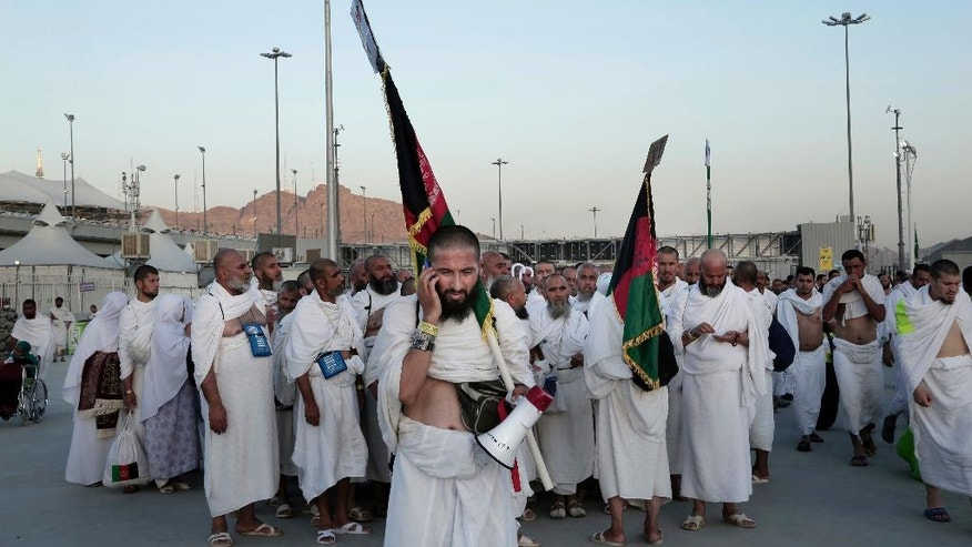 """Afghan Muslim pilgrims make their way to cast stones at a pillar symbolizing the stoning of Satan, in a ritual called """"Jamarat,"""" the last rite of the annual hajj, on the first day of Eid al-Adha, in Mina near the holy city of Mecca, Saudi Arabia, Monday, Sept. 12, 2016. (AP Photo/Nariman El-Mofty)"""