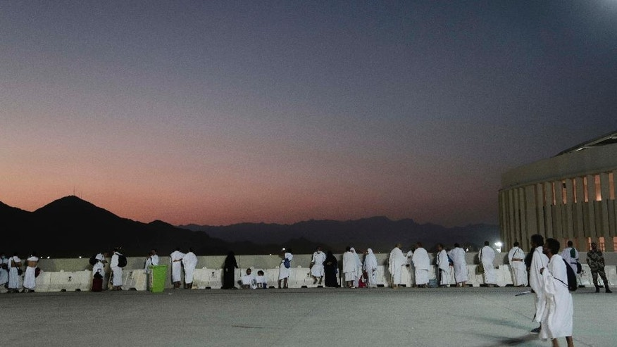 "Muslim pilgrims watch sunrise before they make their way to cast stones at a pillar symbolizing the stoning of Satan, in a ritual called ""Jamarat,"" the last rite of the annual hajj, on the first day of Eid al-Adha, in Mina near the holy city of Mecca, Saudi Arabia, Monday, Sept. 12, 2016. (AP Photo/Nariman El-Mofty)"