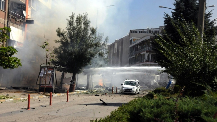 Firefighters work to extinguish a fire after a car bomb attack in the city center of Van.