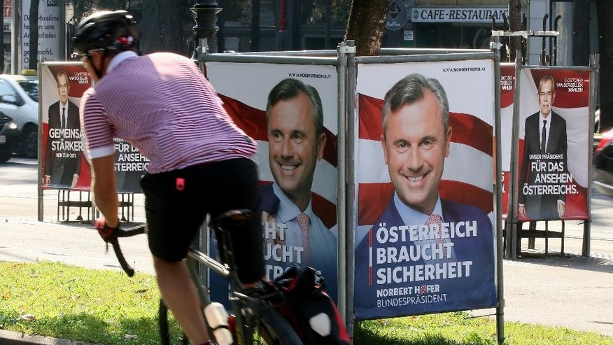 A man cycles between election posters of Alexander Van der Bellen, candidate for presidential elections and former head of the Austrian Greens,  left and right, and Norbert Hofer, candidate for presidential elections of Austria's right-wing Freedom Party, FPOE, center, in Vienna, Austria, Monday, Sept. 12, 2016.  A second attempt to elect Austria' president this year was postponed Monday, with the country's interior minister saying the move was dictated by the discovery that the envelopes of absentee ballots frequently could not be sealed because of faulty adhesive strips. The delay must still be formalized through a still-to-be-created law. But in asking the government do draft such legislation, Interior Minister Wolfgang Sobotka effectively canceled plans to hold the vote Oct. 2.  Poster in center reads: Austria needs Security.  (AP Photo/Ronald Zak)