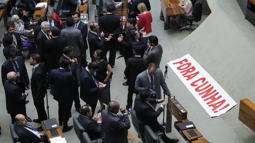 """A banner that reads in Portuguese """"Temer Out!"""" is placed on the floor of the Chamber of Deputies during the trail of former President of the Chamber of Deputies Eduardo Cunha, in Brasilia, Brazil, Monday, Sept. 12, 2016. Brazilian lawmakers are deciding whether a key ally of President Michel Temer should be stripped off his seat amid accusations of corruption and obstruction of justice.(AP Photo/Eraldo Peres)"""