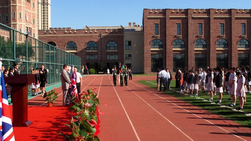 In this Aug. 31, 2016 photo, Chinese paramilitary policemen carrying national flag march on the running track for a flag raising ceremony during the opening of the Haileybury College's Chinese campus in northern China's Tianjin Municipality. International schools from outside China are booming thanks to growing demand from Chinese parents seeking different pathways for their children to college abroad. Top prep schools are opening campuses in China and catering to students who want to go to university in the West. Getting into China's best public high schools can be monumentally difficult and many parents are opting to pay for what they see as a less stressful and more enriching experience at an international school. (AP Photo/Nomaan Merchant)