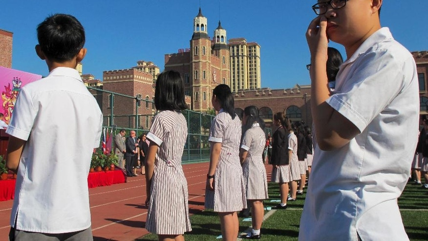 In this Aug. 31, 2016 photo, Chinese student gather on a field as they attend the opening ceremony of the Haileybury College's Chinese campus in northern China's Tianjin Municipality. International schools from outside China are booming thanks to growing demand from Chinese parents seeking different pathways for their children to college abroad. Top prep schools are opening campuses in China and catering to students who want to go to university in the West. Getting into China's best public high schools can be monumentally difficult and many parents are opting to pay for what they see as a less stressful and more enriching experience at an international school.  (AP Photo/Nomaan Merchant)