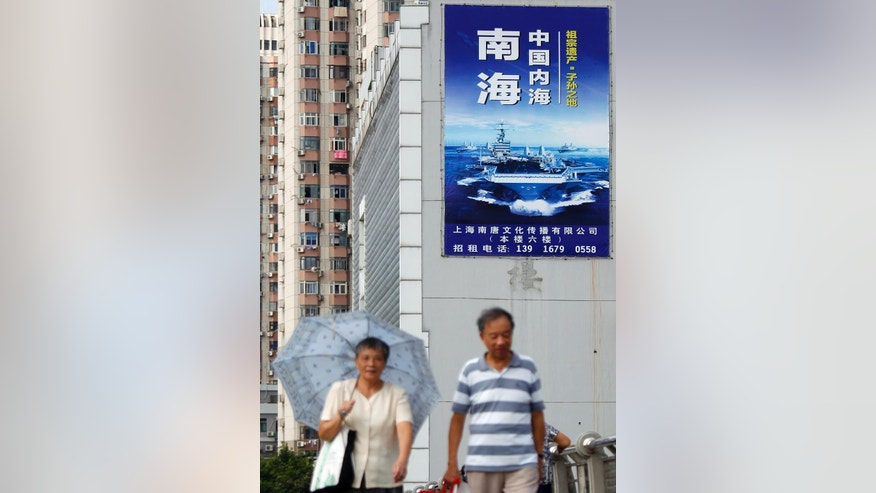 "People walk past a poster that reads ""The South China Sea is China's inland sea"" in Shanghai, China, Monday, Sept. 12, 2016. The Chinese and Russian navies launched eight days of war games in the South China Sea on Monday, in a sign of growing cooperation between their armed forces against the backdrop of regional territorial disputes. (Chinatopix via AP)"