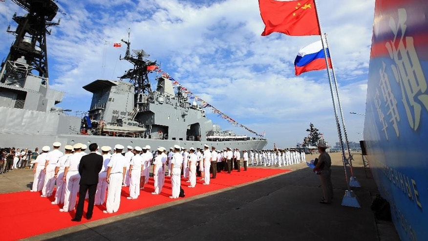 In this photo released by China's Xinhua News Agency, officers and soldiers of China's People's Liberation Army (PLA) Navy hold a welcome ceremony as a Russian naval ship arrives in port in Zhanjiang in southern China's Guangdong Province, Monday, Sept. 12, 2016. The Chinese and Russian navies launched eight days of war games in the South China Sea on Monday, in a sign of growing cooperation between their armed forces against the backdrop of regional territorial disputes. (Zha Chunming/Xinhua via AP)